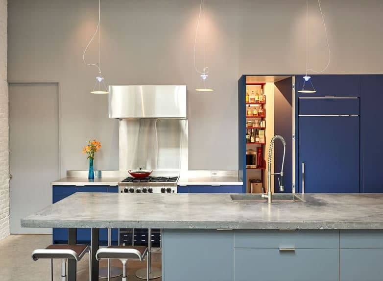 This kitchen is a combination of modern elements with the industrial-style kitchen. It has a kitchen island with modern light blue cabinets with a gray concrete countertop. This pairing is mirrored by the light gray walls and the blue peninsula cabinets.