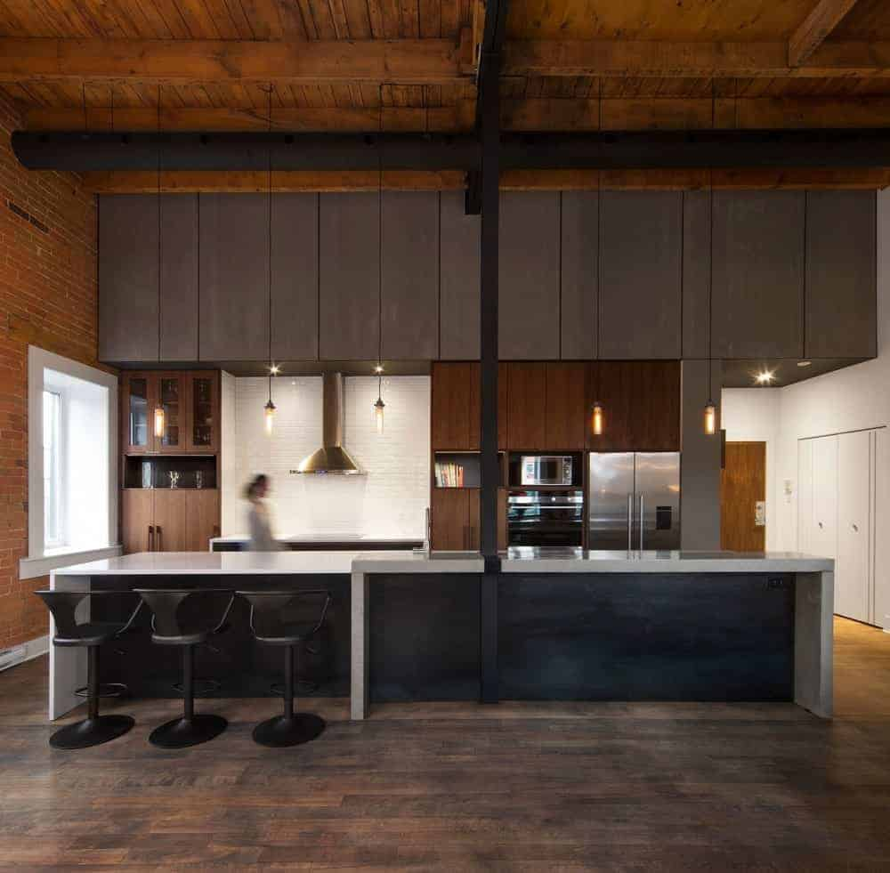 This view of the charming industrial-style kitchen shows a large kitchen island with waterfall white countertops and a black wooden facade pairing with the black stools. This also matches with the black support column and air duct of the high wooden ceiling that has exposed wooden beams.