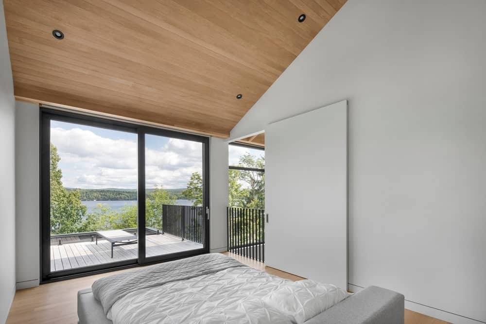 This is a simple Contemporary-style bedroom that has a wooden shed ceiling matching with the hardwood flooring that complements the traditional bed with a light gray frame and white sheets. This light gray bed matches the walls that are brightened by the large glass sliding doors leading to a balcony.