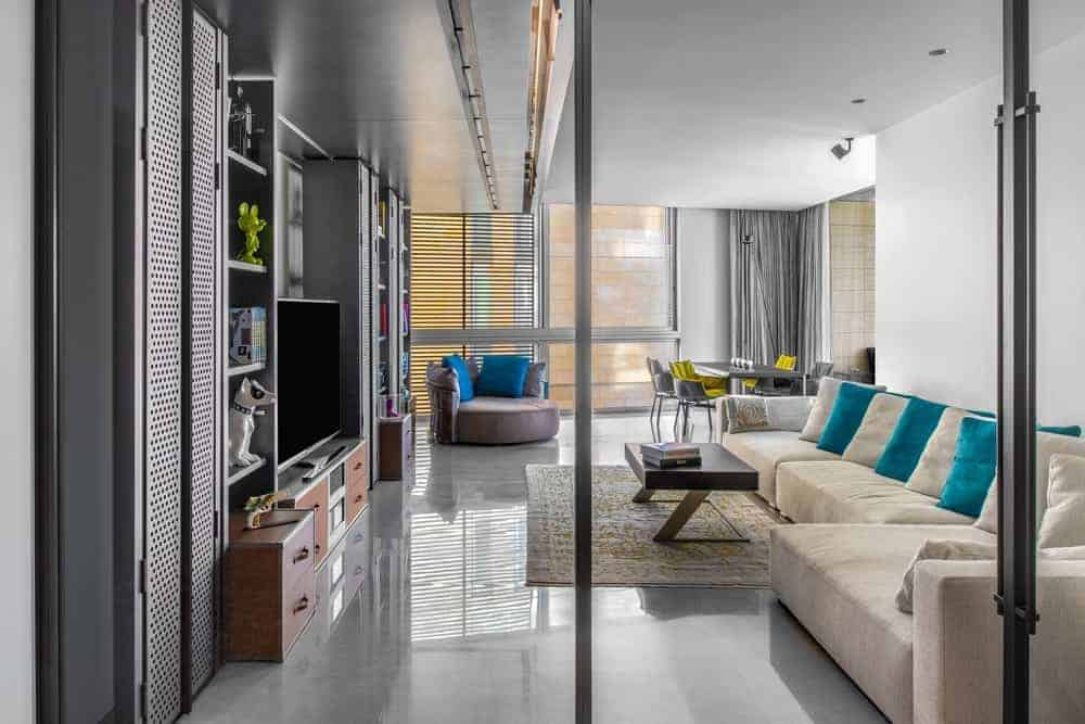 A large velvet beige L-shaped sofa takes over most of the floor space of this industrial-style living room that has a large gray metal structure across from the sofa. This houses the entertainment system and has cabinets and shelves.