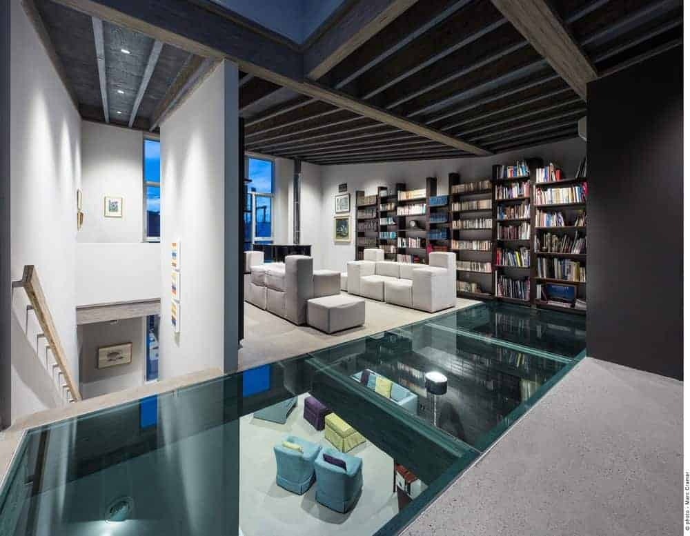 There is a unique glass flooring with a green tint that leads to this living room that is surrounded by multiple bookshelves that match the ceiling with a same dark hue of the shelves. This makes the modern white leather sofa stand out.