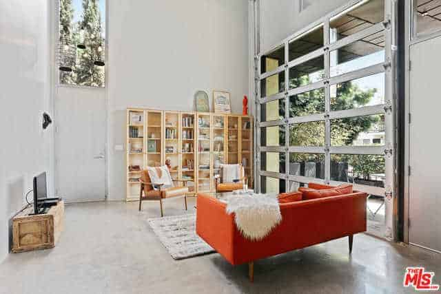 This living room has a bright orange cushioned sofa that stands out against the light hue of the industrial-style flooring and white walls that are adorned with a large bookshelf adjacent to a large roll-up glass door.