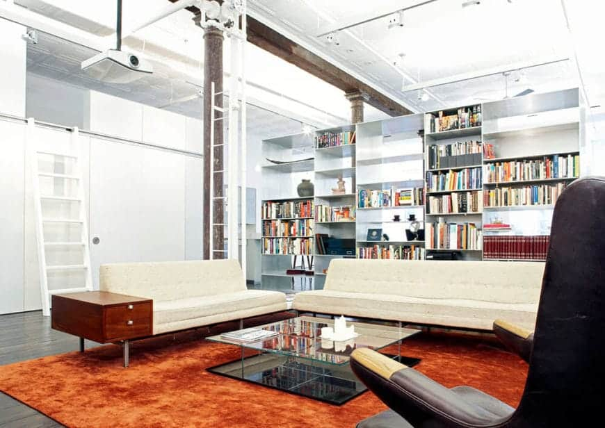 The bright orange velvet area rug stands out against the hardwood flooring and the white walls and ceiling. This ceiling has exposed pipes and wiring as well as a projector above the beige cushioned sofas facing a glass-stop coffee table.