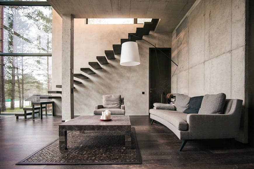 This living room is in a large alcove made of gray concrete ceiling and walls paired with a dark hardwood flooring that is contrasted by the light gray curved sofa and a cushioned armchair facing a rectangular coffee table.