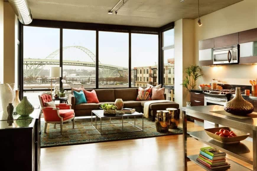 The L-shaped sectional sofa has colorful pillows that match the tufted cushioned armchair beside it. This is given a nice urban background featured by the large glass wall that illuminates the concrete gray ceiling and its exposed vent.