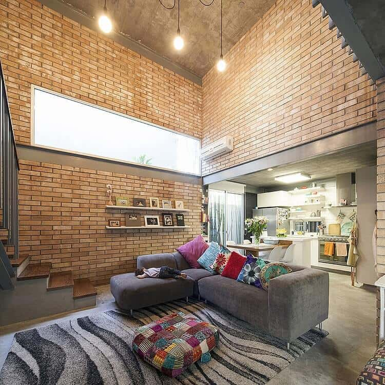 The gray L-shaped sectional sofa stands out against the red brick walls extending all the way up to a high concrete ceiling adorned with a brilliant transom window that augments the warm yellow lights of the pendant lights.