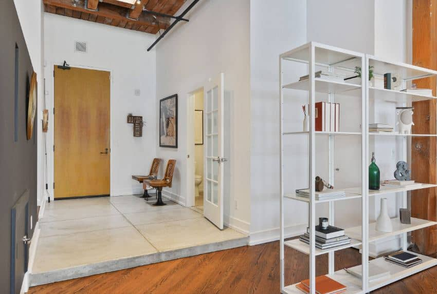 This wooden main door opens to a foyer that has a concrete flooring that complements the white walls and the high wooden ceiling with exposed wooden beams, wires and tubing for that distinctive industrial feel that matches with the rest of the home.