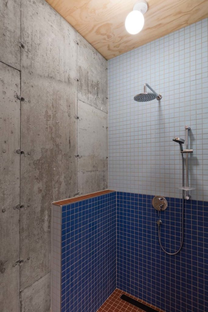 This bathroom has a shower area with small blue tiles on its walls that stand out against the gray concrete walls and bare wooden ceiling that supports a large white flush-mount light that illuminates the stainless steel fixtures of the shower area.