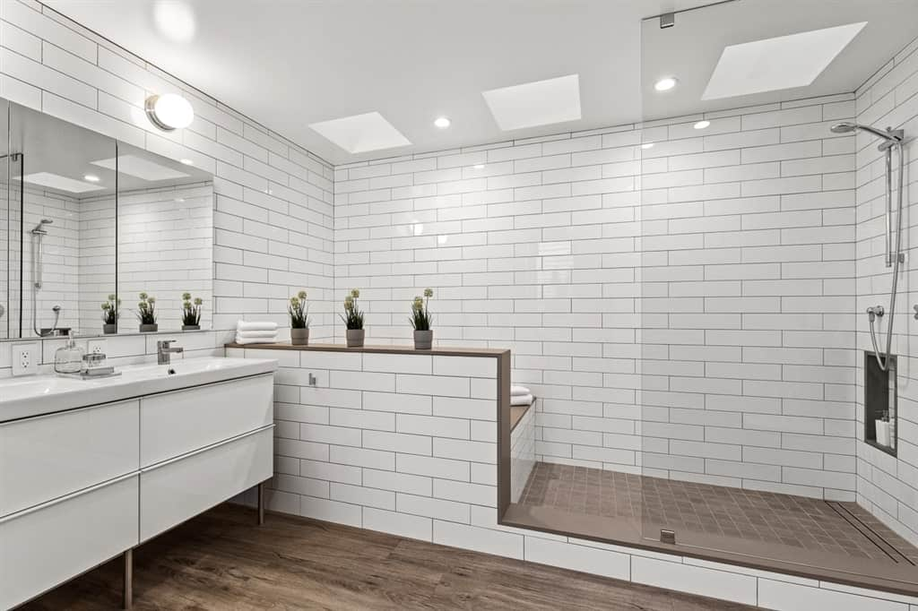 This bathroom has enough space for a bathtub and a shower area on the far wall that is made up of white tiles arranged in a brick wall pattern complemented by the dark wood hue of the flooring tiles of the shower area matching with the hardwood flooring of the vanity area.