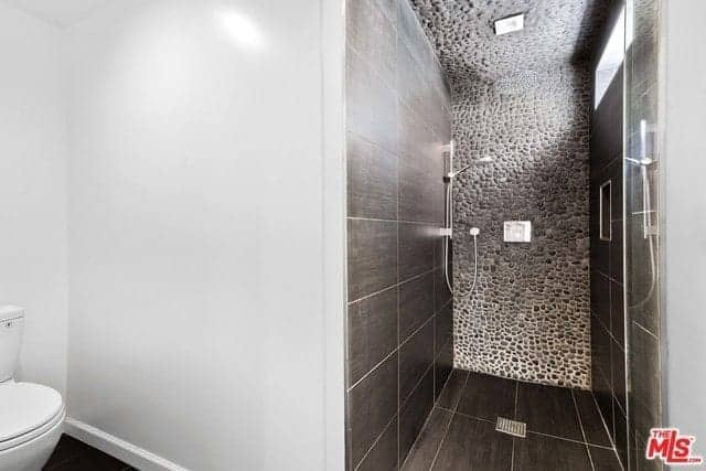 The white porcelain toilet is placed in a corner of white walls. Adjacent to this is the glass door of the shower area that has contrasting dark tiles on its floor and walls except the far wall and ceiling that is made of small stones embedded in concrete.