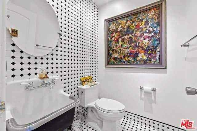 A nice dash of color is provided by the colorful abstract painting mounted on the white wall beside the white toilet that stands out against the patterned black and white hues of the flooring tiles that extend to the wall behind the industrial-style sink and toilet.