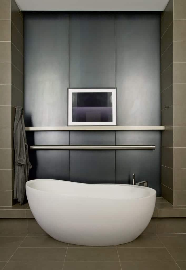 The white freestanding bathtub is paired with a stainless steel faucet matching the stainless steel rod that stands out against the black wall panel that is surrounded by the gray tiles of the flooring and the walls.