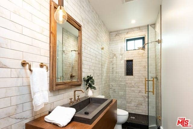 This bathroom has beautiful white marble tiles that are arranged in a brick wall pattern. These tiles extend from the walls of the vanity area to the shower area that has a glass door. The vanity area is adorned with a wood framed mirror and brass fixtures.