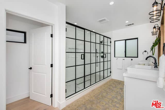 This primary bathroom has a wide shower area enough for two within its glass wall that has black frames that matches with the window and the fixtures of the shower area and vanity area. This has a white sink topped with a wood-framed mirror.