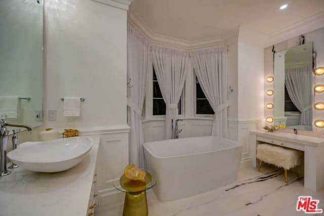The charming nook alcove of curtained windows and white wainscoting is a nice background for the freestanding bathtub that blends with the white marble flooring. Beside this is the white vanity area with a large mirror bordered with yellow spherical lights.