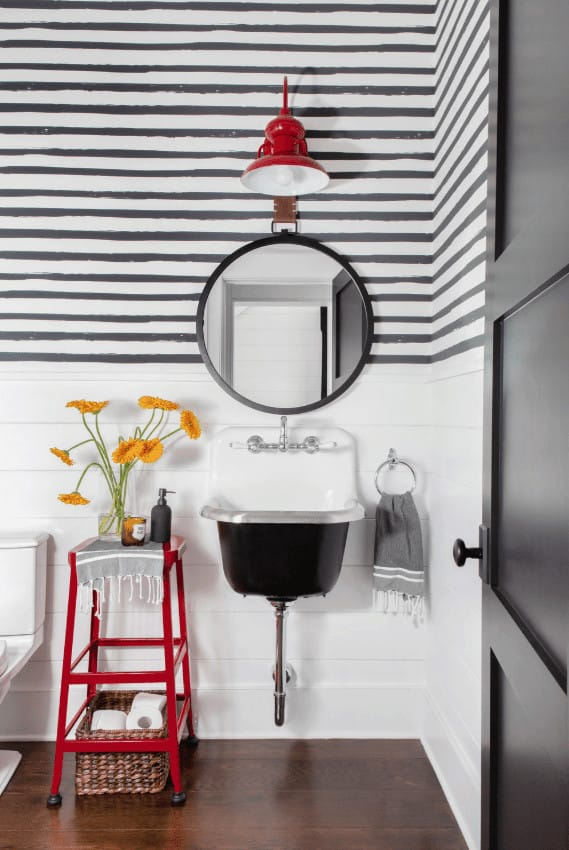 There is a red metal stool that stands out against the white wooden wainscoting that has a wooden plank finish. This stool matches with the red Farmhouse-style wall lamp above the round mirror mounted on the upper walls that have a striped wallpaper finish.
