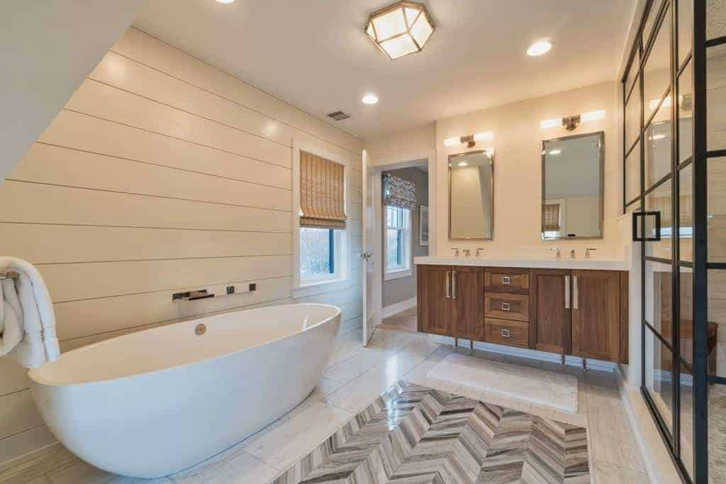 The white freestanding bathtub is against a wall with a white wooden plank finish warmed by the yellow lights of the wall-mounted lamps above the vanity mirrors above the wooden vanity that has shaker cabinets and drawers that stand out against the light hue of the flooring.