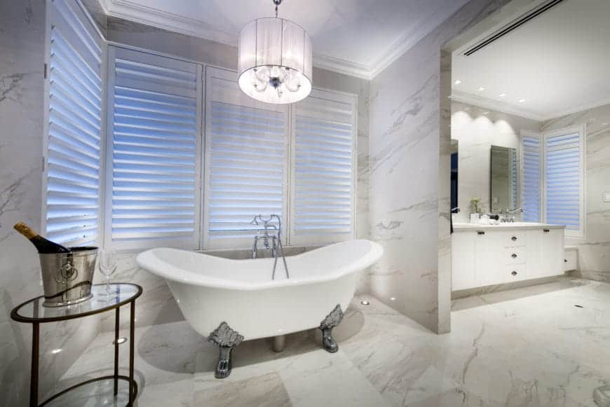 The elegant freestanding bathtub has silvery legs with intricate carvings on it. This is placed in an alcove of white marble walls and flooring surrounded by white shuttered windows topped with a small white chandelier with a round hood on it.