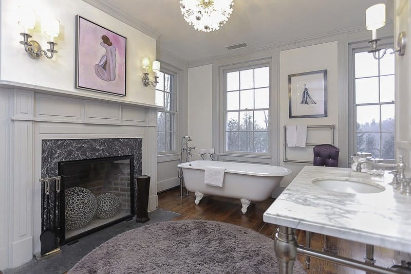 This is an elegant and warm Farmhouse-style primary bath that has a white freestanding bathtub that stands out against the dark hardwood flooring beside the fireplace with a light gray mantle topped with a colorful painting across from the vanity area.