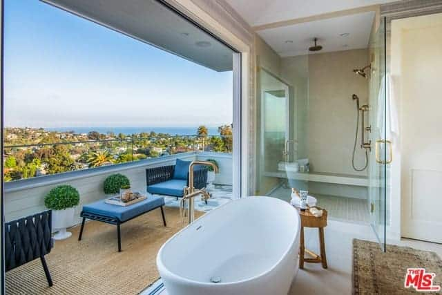 The wall beside the freestanding bathtub opens up to a bright veranda that has a sitting area of armchairs and coffee table with blue cushions. This brings in an abundance of natural lighting to the glass-enclosed shower area by the head of the bathtub.