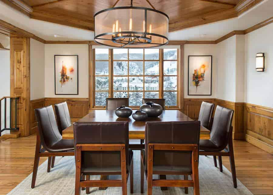 The charming brown leather cushioned chairs are a perfect complement for the wooden dining table that matches with the wooden wainscoting of the white walls. This aesthetic is mirrored by the white ceiling that has a wooden central tray.