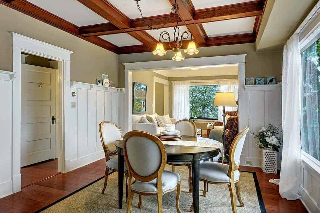 The hardwood flooring that is topped with a rustic woven area rug matches with the exposed wooden beams of the white ceiling. This is reflected by the white wainscoting contrasted by the green upper walls of this medium-sized dining room.