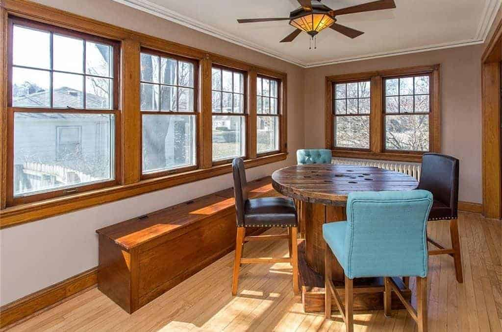 The highlight of this medium-sized dining room is the rustic round wooden table that is a repurposed cable reel. This matches the warm homey quality of the light hardwood flooring, long bench with storage and the frames of the windows that bring in natural lights.