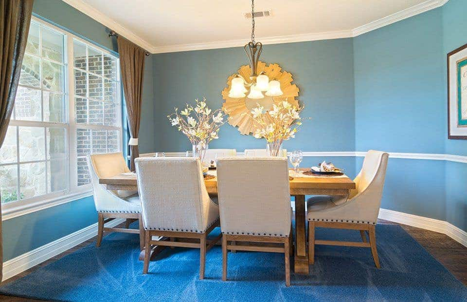 This medium-sized dining room has a rectangular wooden table in the middle of the blue area rug encircled by light gray cushioned chairs. This is given a nice background of light blue walls and white ceiling brightened by the chandelier and the French windows.
