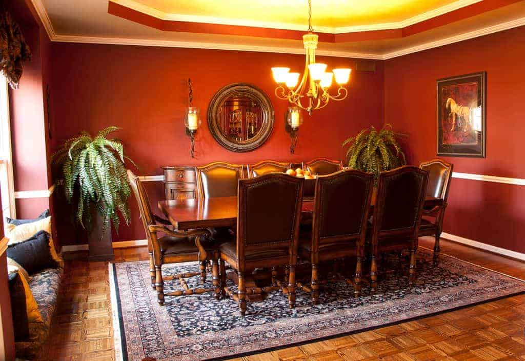 The antique-style rectangular wooden dining table is paired with brown leather cushioned chairs. These are a match with the dining room cabinet and the round wall-mounted mirror above it brightened by the warm yellow lights of the chandelier.