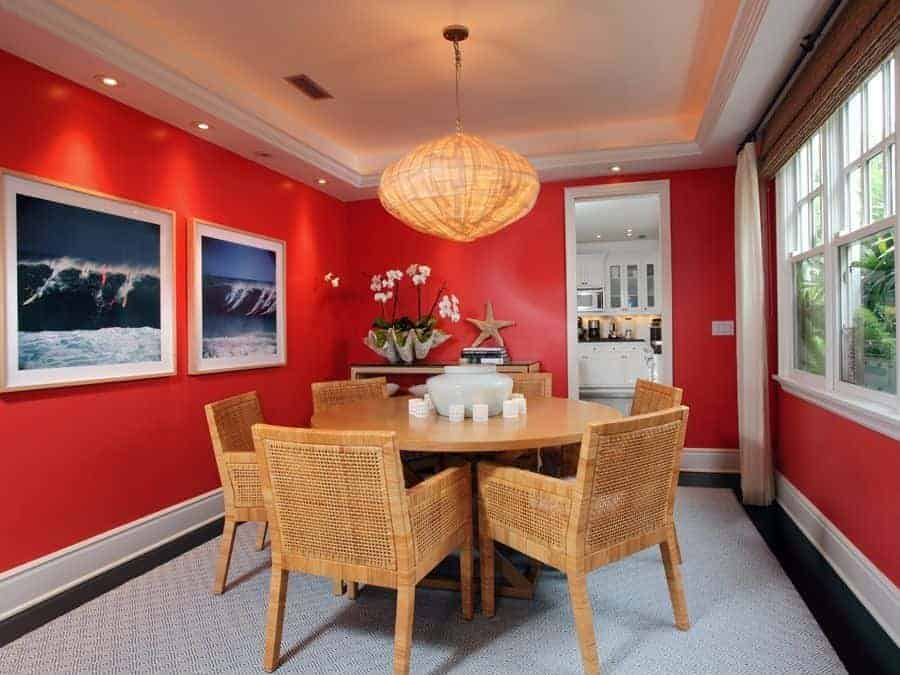 This beach-style dining room has bright red walls adorned with a couple of framed photos depicting surfers riding a large wave. Adjacent to it is a console table with flowers planted on a large seashell beside a woven wicker starfish that matches the dining set and the pendant light.