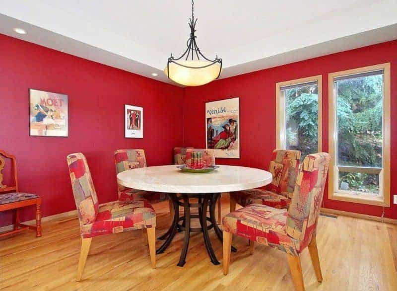 The charming framed vintage posters and artworks area a nice accent for the red walls that is contrasted by a bright white ceiling with recessed lights and a pendant light in the middle hanging over the white round dining table paired with cushioned chairs with colorful patterns.