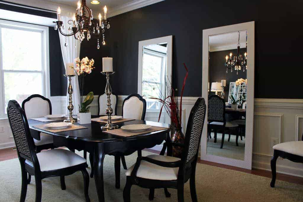 This elegant and formal dining room has black walls contrasted by the white wainscoting and the pair of large rectangular mirrors leaning against the wall by the black wooden dining table and its matching dining chairs with white leather cushions.
