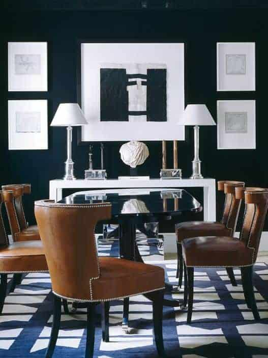 The brown leather cushioned wing back chairs serve as a medial element to the contrasting black and white elements like the black dining table and black walls contrasted by the white console table and wall-mounted framed artworks.