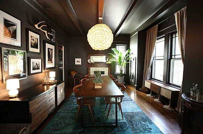 The peculiar spherical pendant light stands out against the black wooden ceiling with exposed wooden beams and the walls that are mostly accented with framed photographs and paintings. the green patterned area underneath the dining set provides a nice dash of color.