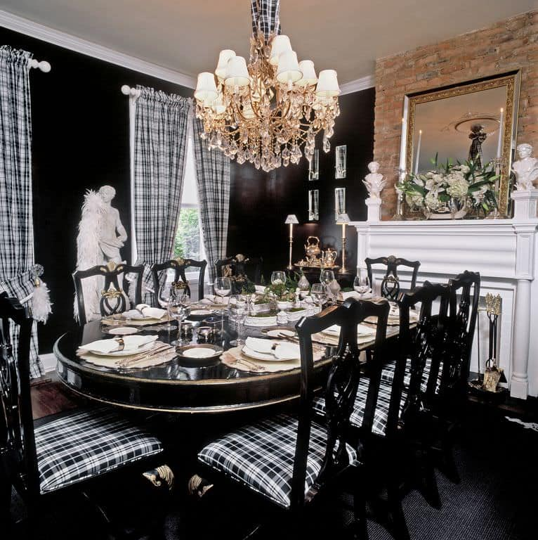 The white mantle of the fireplace stands out against the black walls and the black dining table that is paired with black wooden chairs that have plaid seat cushions matching the curtains flanking the tall windows by the marble statuette.