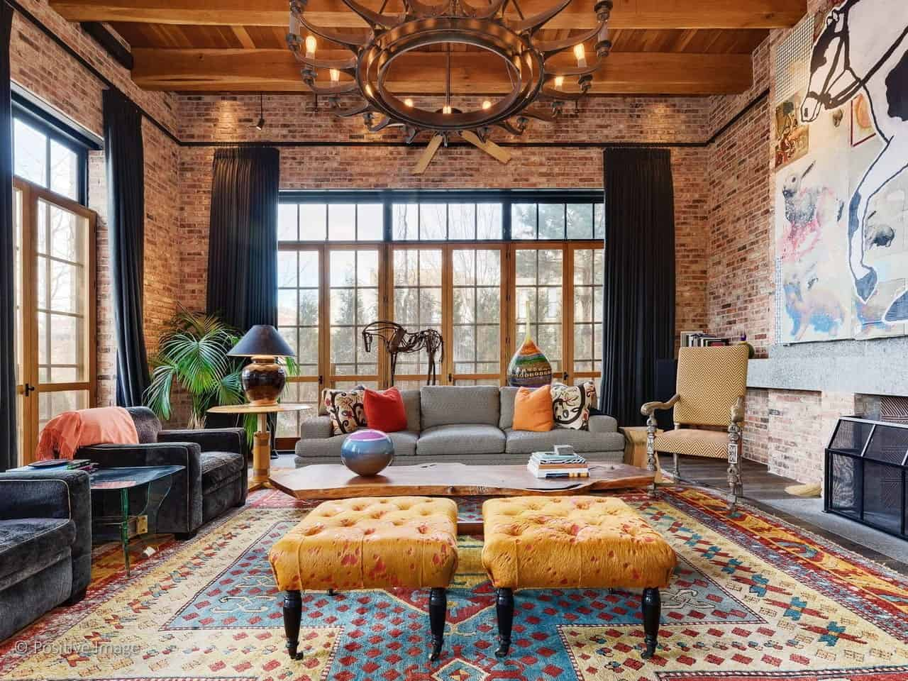 Industrial-style living interior with exposed brick walls, candelabra chandelier, beam ceiling, and colorful area rug.