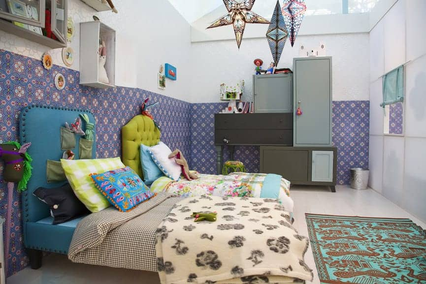 Shared kids bedroom boasts gorgeous blue and green beds along with modular cabinets that are placed against the white walls dominated by lovely floral wallpaper.