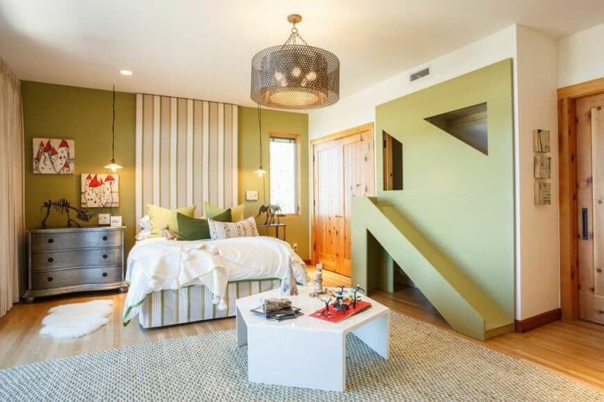 Kids bedroom illuminated by bulb pendants and a perforated drum chandelier that hung over the white sleek table sitting on a non-slip rug. It has a green slide and a striped bed accompanied by wooden drawer chest and nightstand.