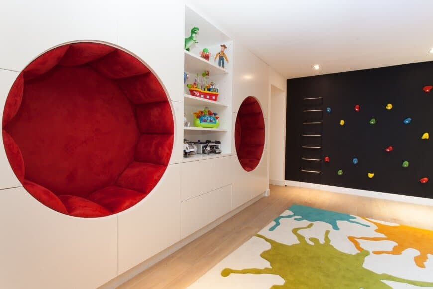 Fun bedroom with an eye-catching area rug and a black climbing wall accented with multicolored rocks. It has inset shelving and a pair of round nooks fitted with red velvet cushions.
