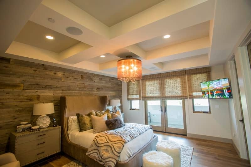 Primary bedroom with a beautiful coffered ceiling along with a rustic wall. The room features hardwood flooring and an elegant bed setup.