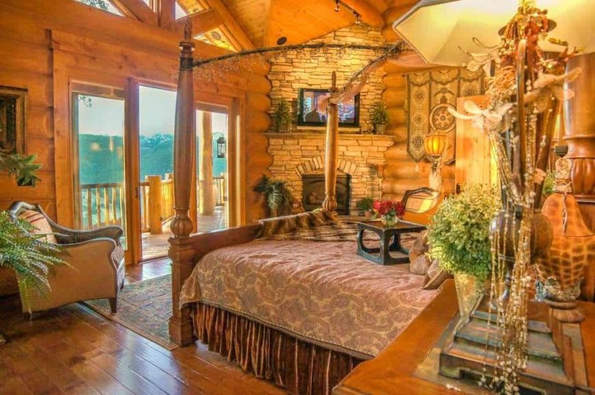 Large primary bedroom with rustic walls, ceiling and flooring. It has an elegant bed setup and a stone fireplace with a TV on top. The warm lighting looks so perfect together with the bedroom's rustic style.