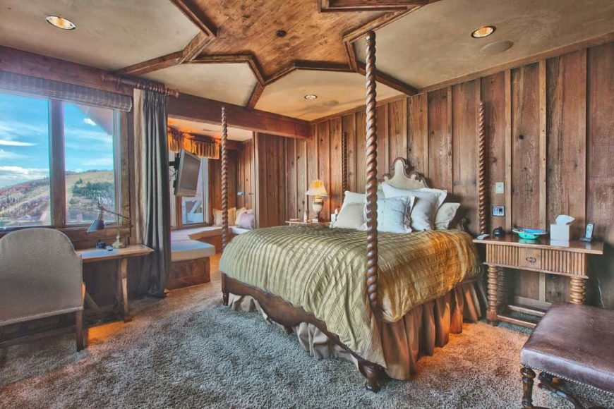 Primary bedroom featuring a stylish rustic-design on the ceiling. It has wooden walls and thick carpet flooring. The room offers a cozy bed and a rustic office desk area, along with a sunroom.