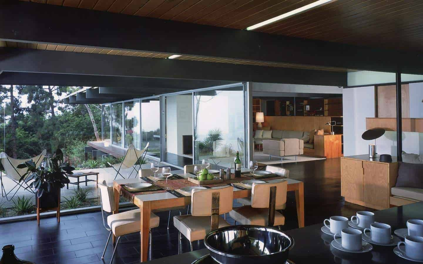 This dining room is right beside the kitchen that has the same black flooring tiles and black exposed wooden beams of the brown wooden ceiling with a shiplap design. These black elements make the wooden dining table and its beige chairs stand out.