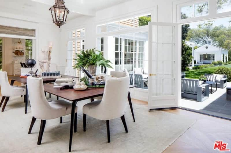 The patio scene outside the French glass windows and glass doors bring in natural lighting that brightens up the white ceiling with exposed beams that support a classic lantern-like pendant light that that brings a certain Spanish-style flair to the bright aesthetic.