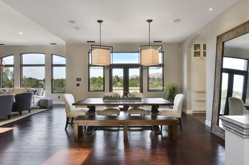 Upon entry of the glass doors of this house, you will see the dining area beside the living room area. The dining set is comprised of a wooden dining table. a wooden bench and four white cushioned chairs. These stand out against the redwood flooring.