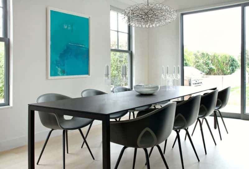 This dining room has a simple dining set that is comprised of a long modern black rectangular table and modern black dining chairs. This stands out against the beige flooring and white walls that is adorned with a blue painting flanked by bright windows.