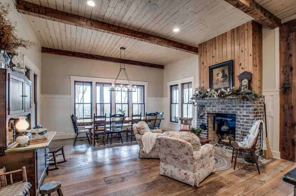 The simple and homey aura of this medium-sized dining room is augmented by the sitting area beside it that has a classic bricked fireplace. The long rectangular wooden table matches with the hardwood flooring and then paired with wooden chairs.