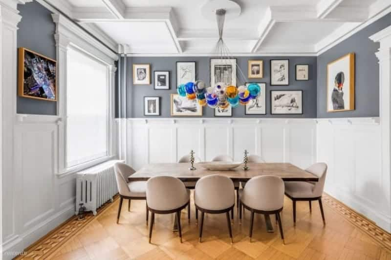 The bright wainscoting of this medium-sized dining room matches with the white coffered ceiling and is complemented by the hardwood flooring that has a subtle checkered design in the middle bordered with intricate designs. This goes well with the beige cushions of the dining chairs paired with the wooden table topped with colorful pendant lights.