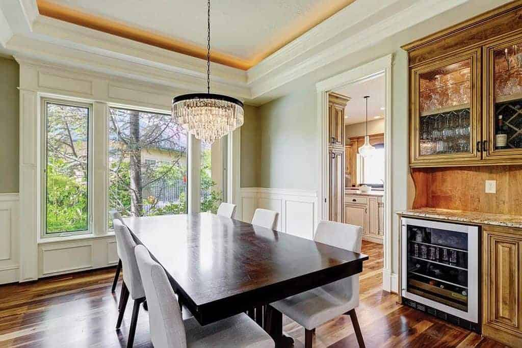 The dark wooden rectangular dining table is matched in elegance by the crystal pendant light hanging from the white tray ceiling. This matches with the white wooden finishing of the walls brightened by a large glass window.