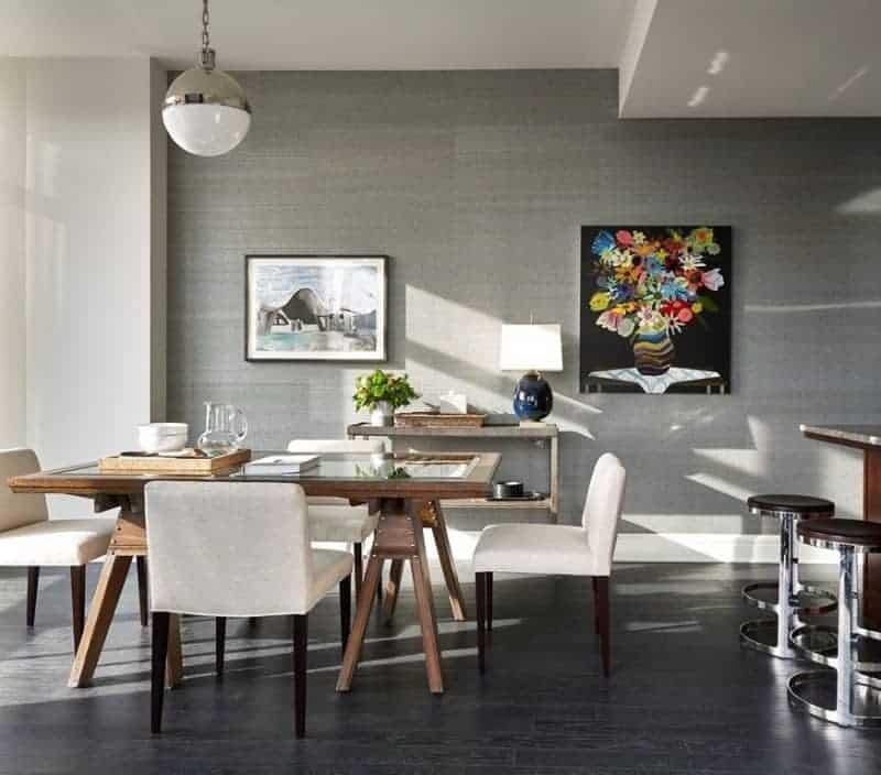 A modern spherical pendant light hangs over the wooden dining table with a glass panel on top. This is paired with dining chairs with dark wooden legs and white cushions that stand out against the gray wall adorned with a console table and a couple of colorful paintings.